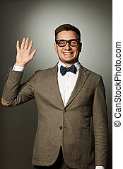 Nerd in eyeglasses and bow tie says Hello against grey...