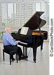 senior pianist - senior man playing on a grand piano at home