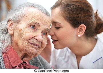 Nursing home - Female nurse is speaking in senior woman ear