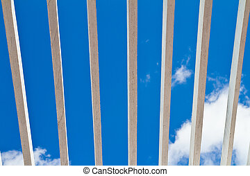 Wooden window grilles and blue sky in background