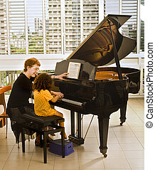 the piano teacher - senior piano teacher with young girl...