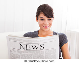 Woman Reading Newspaper - Young Happy Woman Reading...