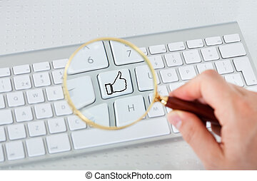 Looking at like key through magnifying glass - Close-up of...