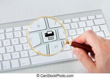 Looking at printer key through magnifying glass - Close-up...