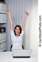 Young girl cheering on a computer - Young woman raises her...