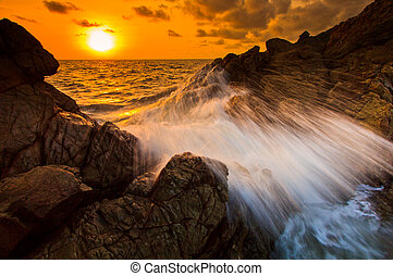 sunset sea waves line impact rock on the beach