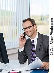 Smiling businessman talking on the phone as he sits at his...