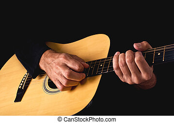 Man playing acoustic guitar in low light environment...