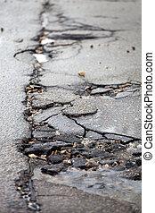 Broken pavement and pothole asphalt road after winter. -...