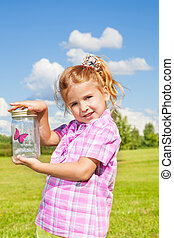 Lilttle girl holds jar with buterfly - Little happy 6 years...