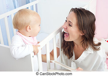 Portrait of a happy mother laughing with cute baby in crib -...