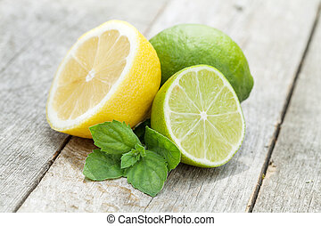 Fresh ripe citruses with mint on garden wood table