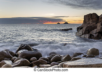 Dusk at Porth Nanven Cove - Waves rushing over rounded...