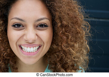Portrait of a young woman smiling with happy expression on...