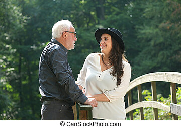 portrait of a father smiling with daughter outdoors -...