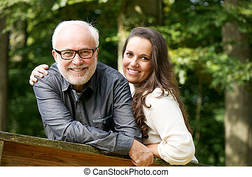 Happy mature man smiling with young woman - Portrait of a...
