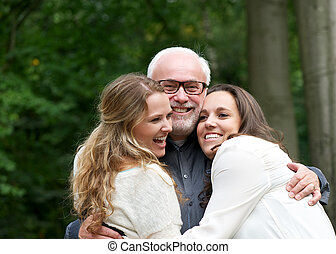 Portrait of a happy family with father and two daughters -...