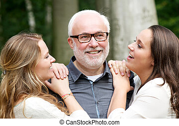 Father smiling with his two daughters outdoors - Portrait of...