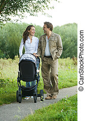Happy mother and father pushing baby pram outdoors -...