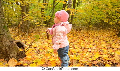 Cute Little Baby Girl is Playing with Yellow Leafs in Autumn...
