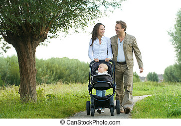 happy mother and father walking with baby in pram