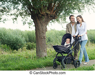 Mother and father walking outdoors and pushing baby in pram...