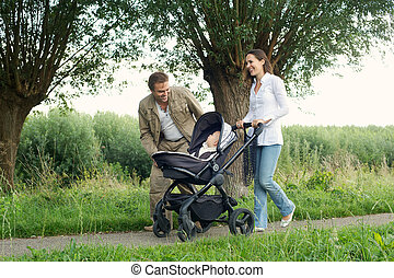 Happy mother and father walking outdoors with baby in pram