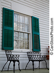 Wrought Iron Benches Under Green Shutters - Two wrought iron...