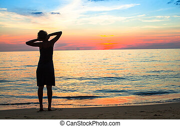 Young woman at the seaside during sunset.