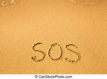 SOS - written in sand on beach texture, soft wave of the sea.