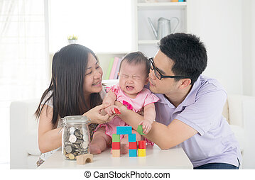 crying asian baby being comforted by chinese parents