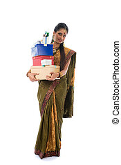 Portrait of a woman in traditional saree holding gifts and smiling