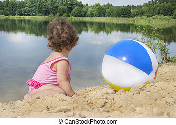 In the summer, on the beach near the lake in the sand little girl playing with a ball