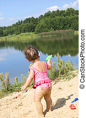 In the summer, on the beach near the lake in the sand little girl playing with toys