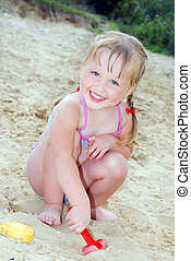 In the summer, on the beach near the lake in the sand little girl playing with toys shovel