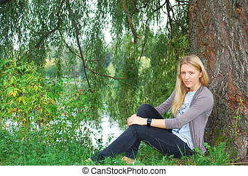the girl sitting near willow near the lake.