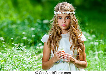 Beautiful pre teen in green field. - Portrait of cute blond...
