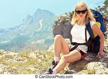 Young Woman Traveler with backpack relaxing on Mountain summit rocky cliff  with aerial view of Sea on background Hiking and Healthy Lifestyle concept