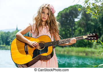 Cute girl playing guitar at lake.