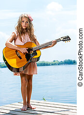 Cute girl standing with guitar at lake.