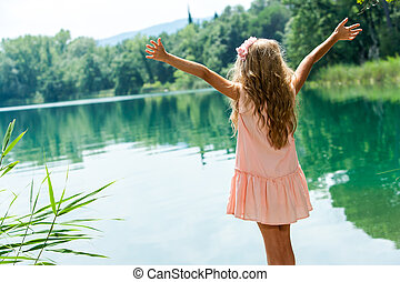Girl standing at lakeside with open arms.