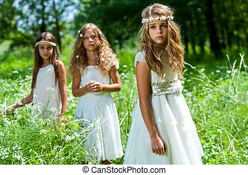 Three girls wearing white dresses in woods. - Portrait of...