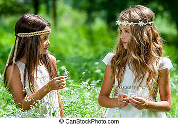 Two girls standing in flower field. - Close up portrait of...