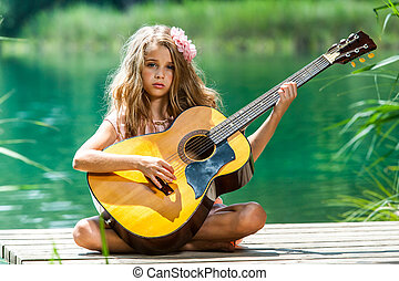 Young girl with spanish guitar on jetty.