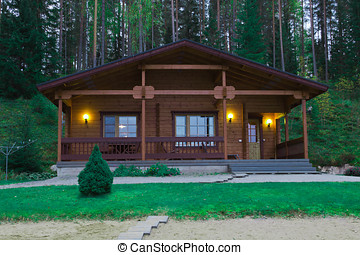wooden cottage - wooden house illuminated at night