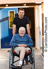 Father and son on a walk - Old father being pushed in his...