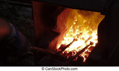 smith at work - smith puts the metal bar into forge furnace...