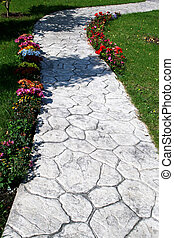 Pathway in garden with flowers and grass