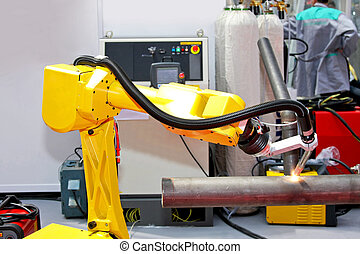 Welding pipe - Yellow robotic arm for automatic welding...