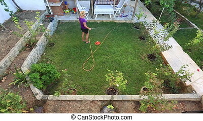gardening - blonde woman watering the garden